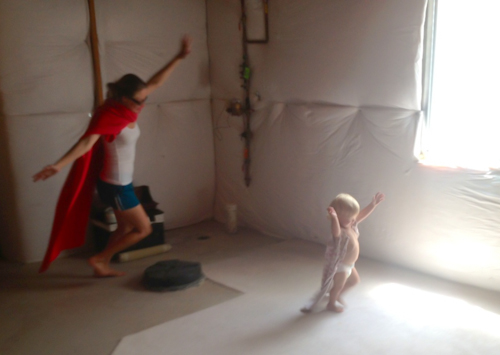 "Playing ""superwoman"" in our unfinished basement (the only cool spot in our house)"